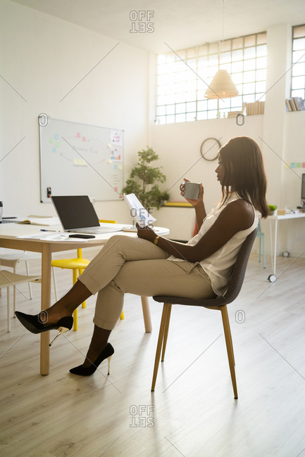 Young woman drinking coffee while analyzing paper at office