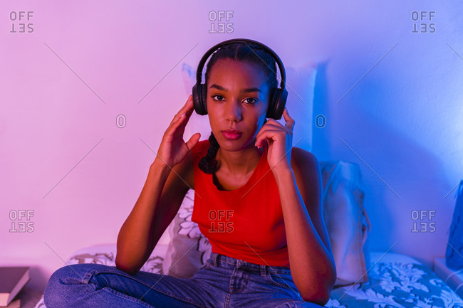Young girl listening music while sitting at home in bedroom