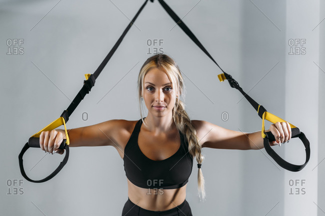 Young sports woman preparing for suspension training in gym