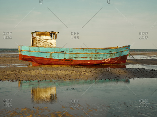 Abandoned fishing boat moored on shore at beach against sky