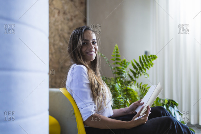 Smiling businesswoman with diary sitting on chair in office