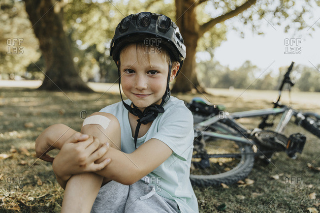 Boy sitting with bandage on knee in pubic park on sunny day
