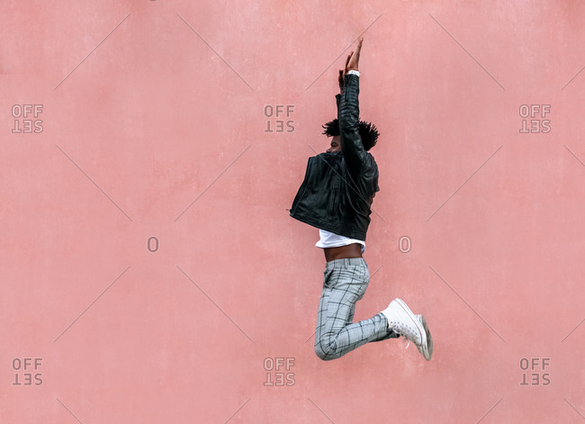 Mid adult man with arms raised jumping by pink wall in city