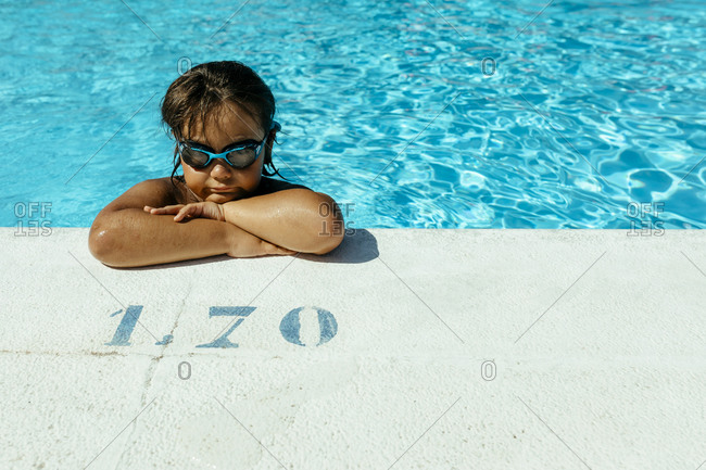 Cute boy with arms crossed leaning at poolside on sunny day