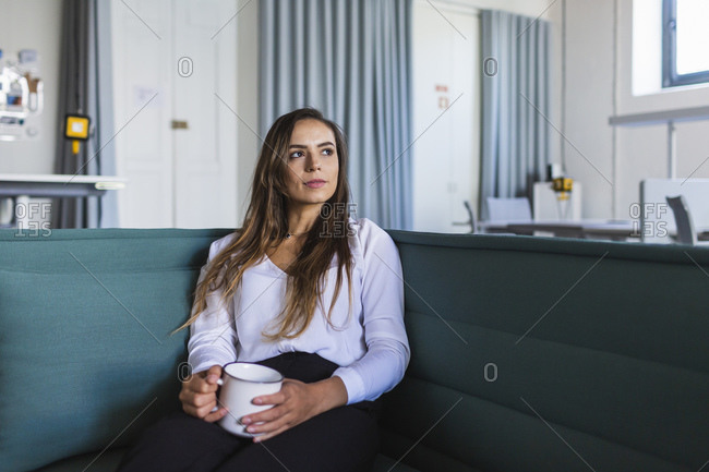 Thoughtful businesswoman with coffee mug on sofa in office