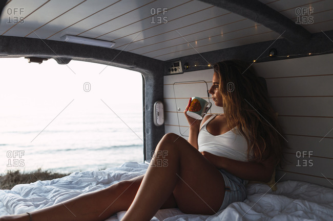 Woman drinking coffee while sitting in camper van at beach