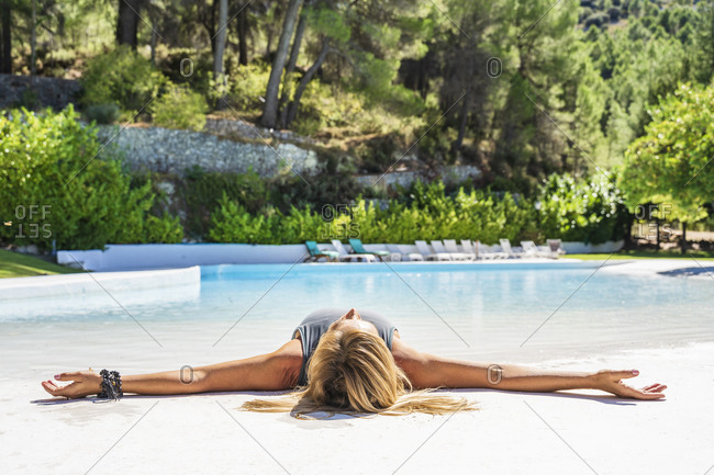 Mature blond woman lying at poolside relaxing on sunny day