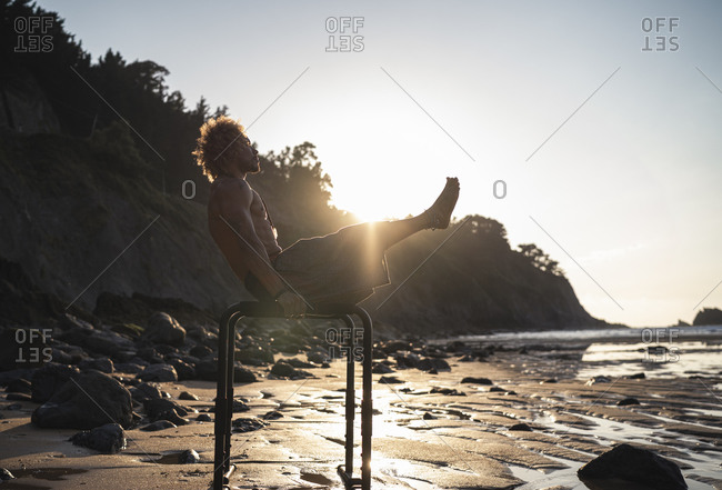 Young man exercising on parallel bars at beach against sky