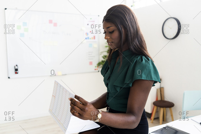Businesswoman checking paperwork while standing at office