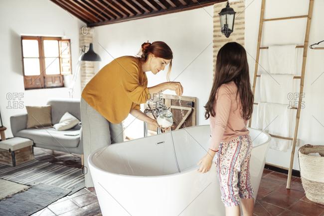 Woman putting bath salt in bathtub while standing at home