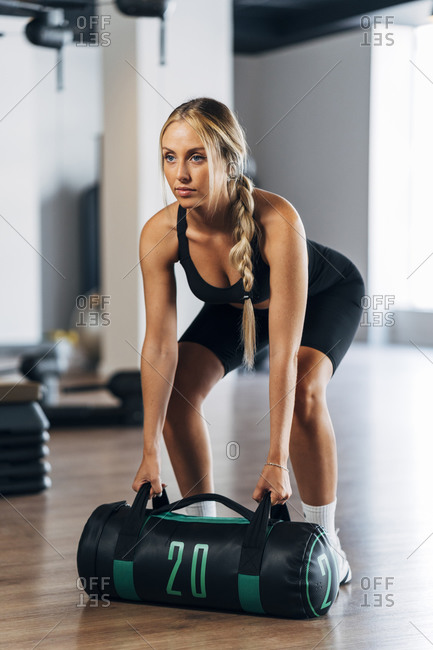 Young female athlete lifting punching bag standing in gym