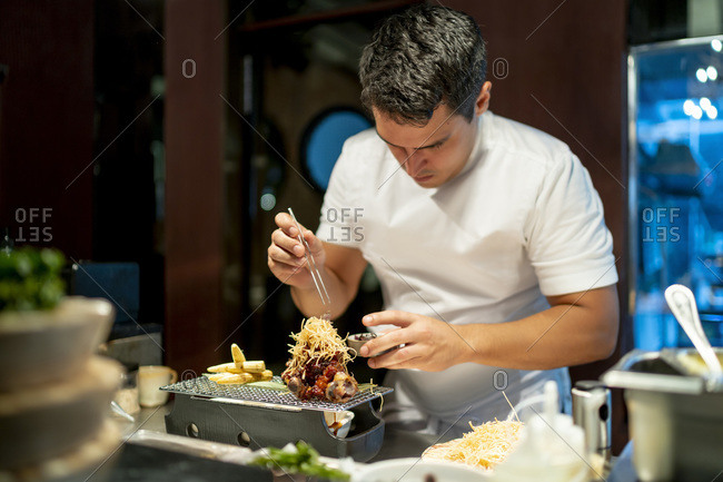 Chef garnishing food while standing in commercial kitchen