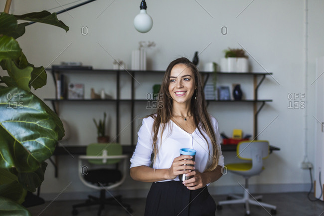 Smiling businesswoman with insulated coffee mug in office