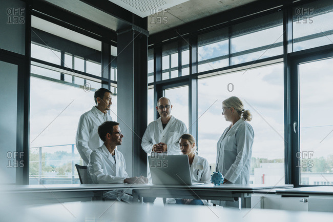 Scientist and doctors discussing while standing in office
