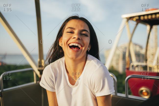 Cheerful young woman enjoying Ferris wheel ride at sunset