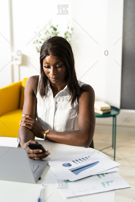 Businesswoman using mobile phone while working at office