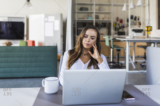 Businesswoman thinking while looking at laptop in office
