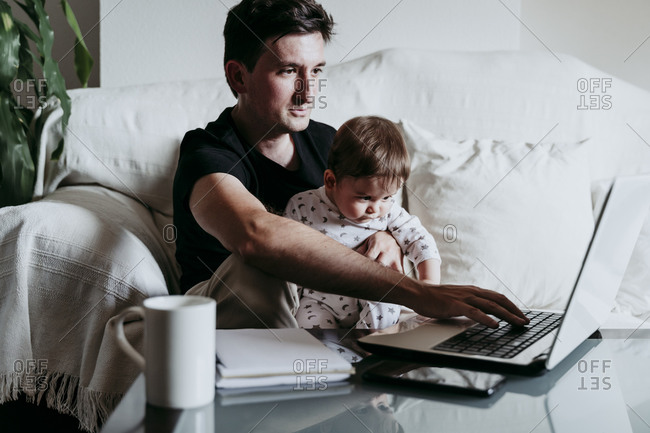 Father using laptop while son sitting on his lap at home