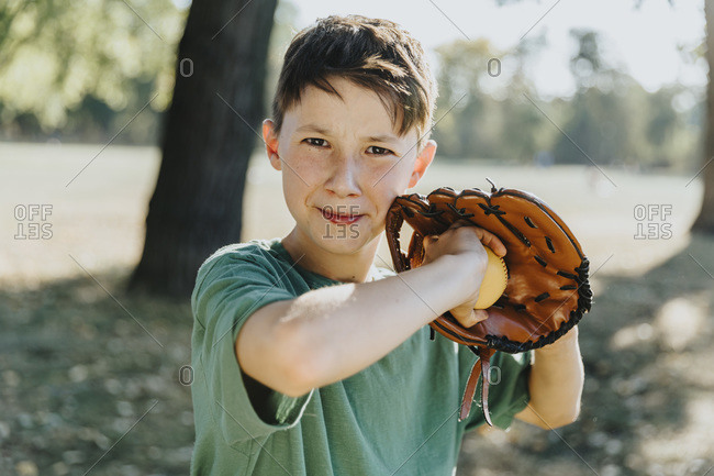 Boy wearing baseball glove while standing in public park