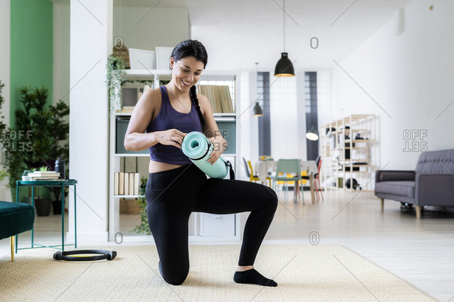 Young woman holding exercise mat while kneeling at home