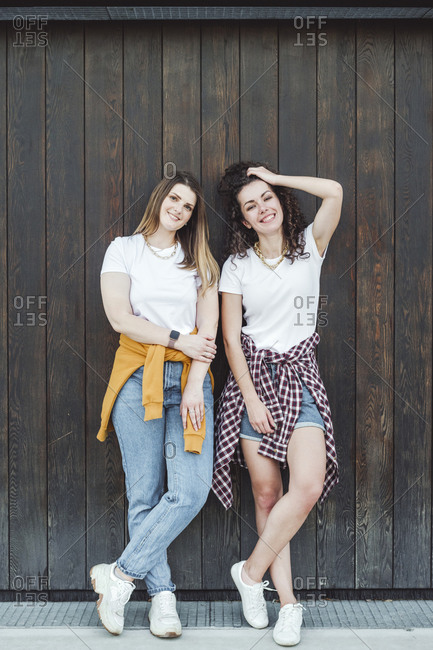 Happy beautiful women leaning against brown wooden wall