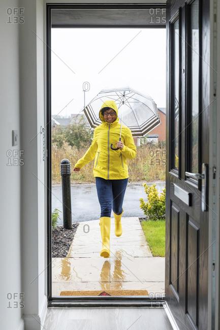 Woman running with umbrella at home during rainy season