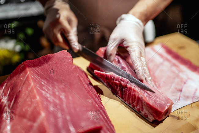 Male chef cutting raw seafood into slices at restaurant