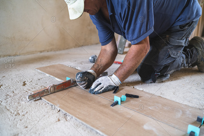 Male manual worker installing parquet flooring in house