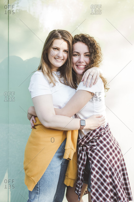 Smiling female friends hugging each other against wall