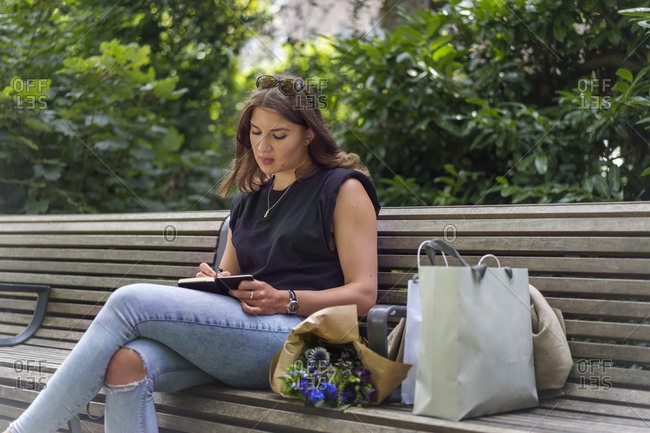 Young woman writing in note pad while sitting on bench