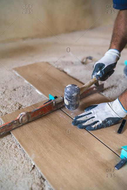 Hand of manual worker hammering parquet floor in house