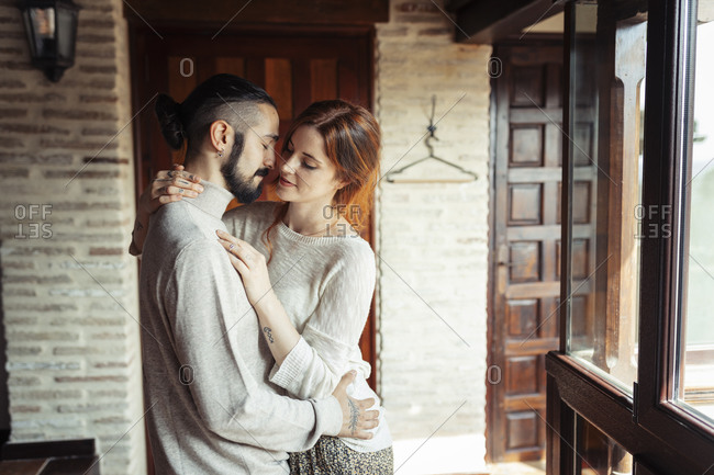Couple doing romance while standing by window at home