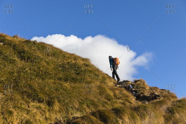 Hiker climbing mountain against blue sky on sunny day