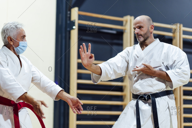 Male student practicing karate by instructor in class