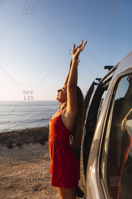 Woman with hand raise standing by camper van at beach