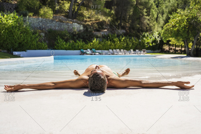 Shirtless man lying at poolside relaxing on sunny day
