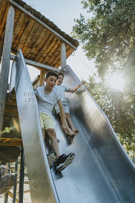 Brothers sliding on slide in public park on sunny day