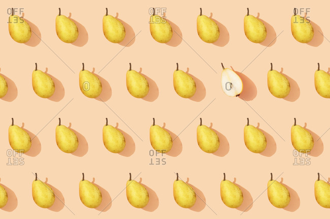 Pattern of fresh yellow pears with single halved one