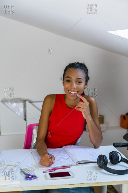 Teenage girl studying while sitting on table at home