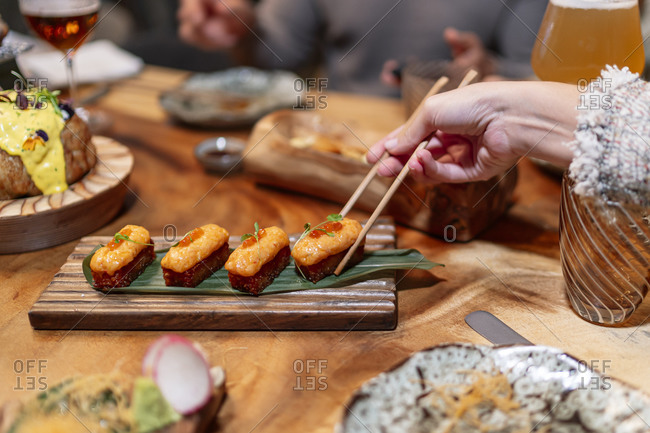 Woman hand taking food with chopsticks at restaurant