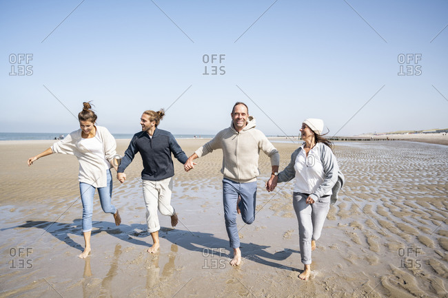 Playful couples holding hands while running on beach