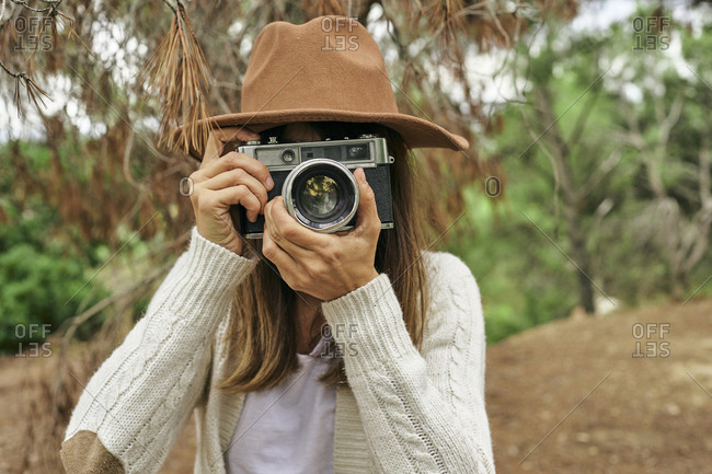 Woman photographing through vintage camera in forest
