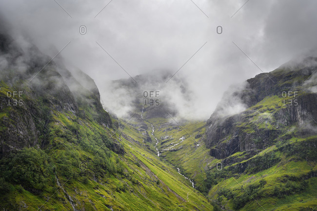 Low clouds floating over stream flowing in Glen Coe