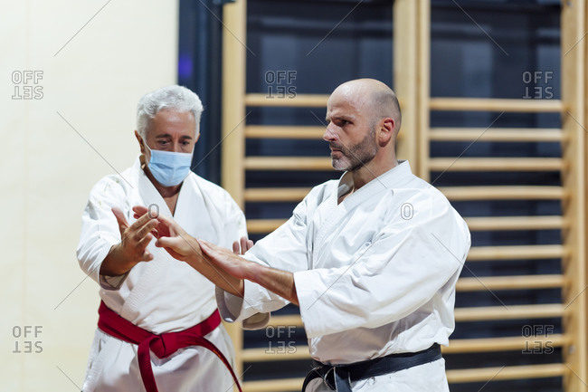 Instructor teaching karate to male student in class