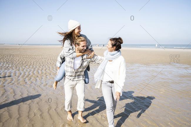 Mother walking with man piggybacking woman at beach