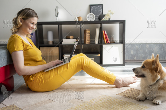 Woman with dog using laptop in living room at home
