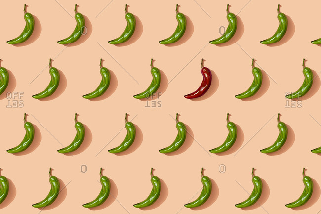 Pattern of green chili peppers with single red one