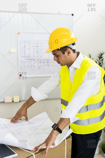 Young male architect analyzing blueprint at office