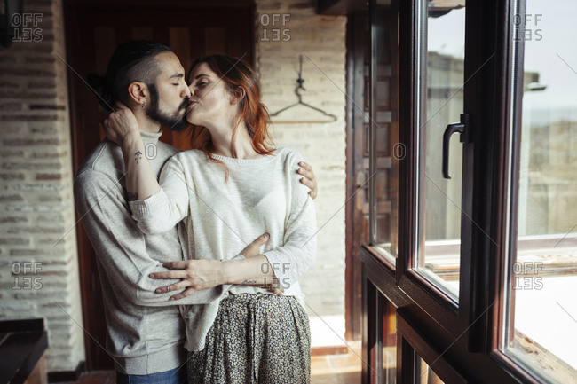 Couple kissing while standing by window at home