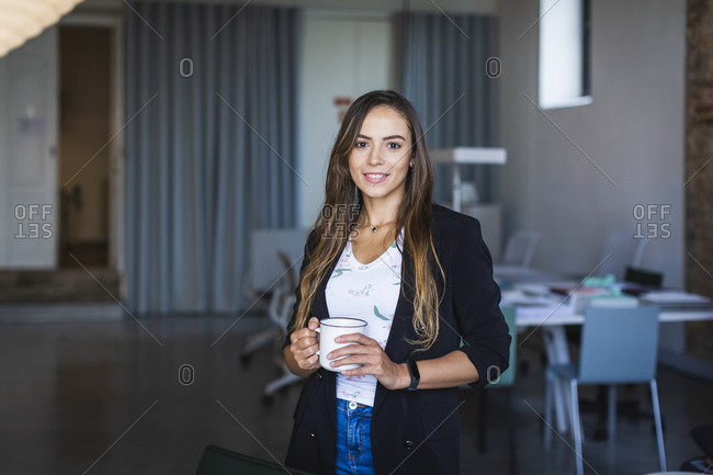 Smiling businesswoman with coffee mug in office
